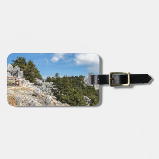 Bench on rocky mountain with trees and blue sky bag tag