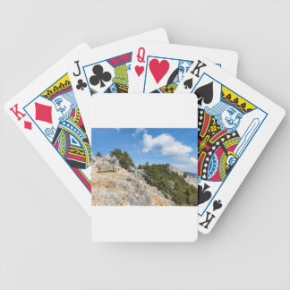 Bench on rocky mountain with trees and blue sky bicycle playing cards