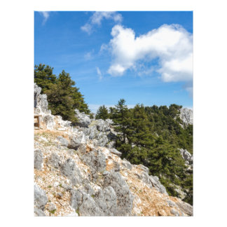Bench on rocky mountain with trees and blue sky letterhead