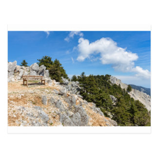 Bench on rocky mountain with trees and blue sky postcard