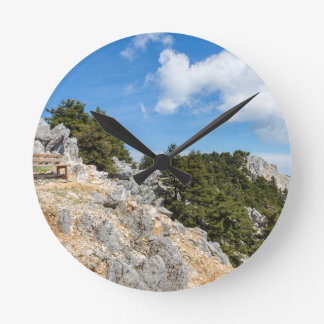 Bench on rocky mountain with trees and blue sky round clock