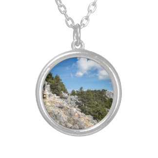 Bench on rocky mountain with trees and blue sky silver plated necklace