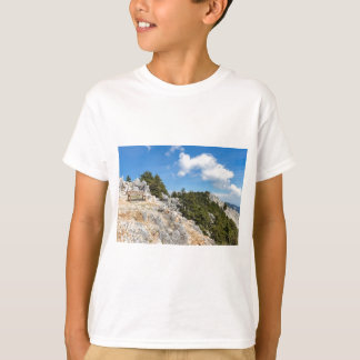 Bench on rocky mountain with trees and blue sky T-Shirt