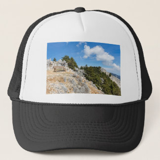 Bench on rocky mountain with trees and blue sky trucker hat
