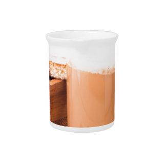 Big mug of hot cocoa with foam pitcher