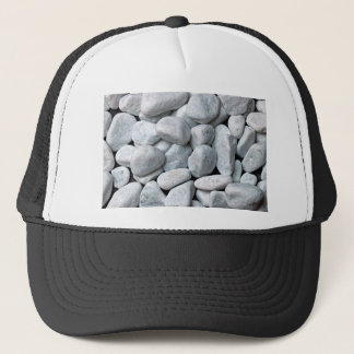 Big pile of gray and white stones from the beach trucker hat