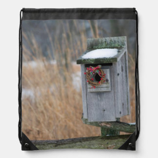 Bird, nest box with holiday wreath in winter cinch bags
