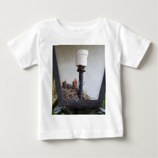 Bird nest in a street lamp. baby T-Shirt