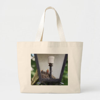 Bird nest in a street lamp. large tote bag