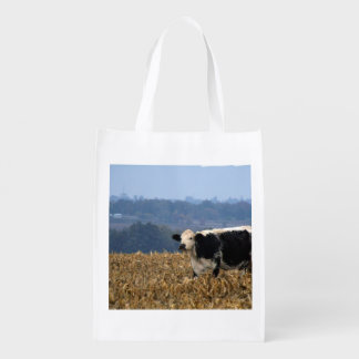 Black and White Cow grazes in freshly plowed field Reusable Grocery Bags