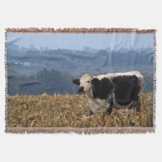 Black and White Cow grazes in freshly plowed field Throw Blanket