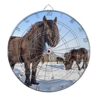 Black frisian horses in winter snow dartboard