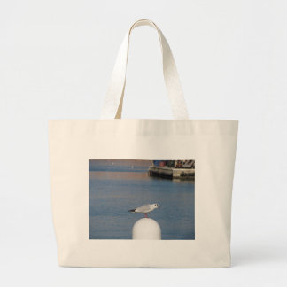 Black-headed gull perched on post calling large tote bag