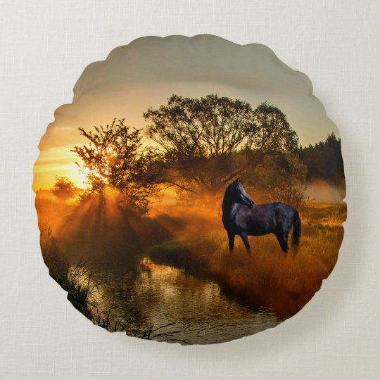 Black horse at sunrise or sunset round pillow