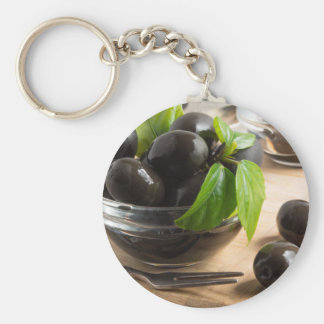 Black olives in a glass bowl on the old vintage basic round button keychain