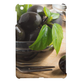Black olives in a glass bowl on the old vintage case for the iPad mini