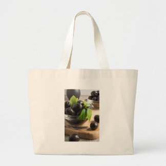 Black olives in a glass bowl on the old vintage large tote bag