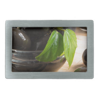 Black olives in a glass bowl on the old vintage rectangular belt buckles