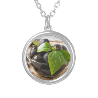 Black olives in glass cups with oil silver plated necklace