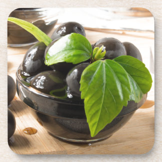 Black olives on a table and glass cups with oil coaster