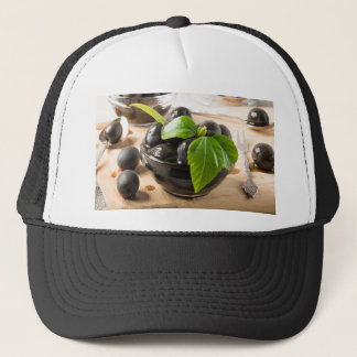 Black olives on a table and glass cups with oil trucker hat