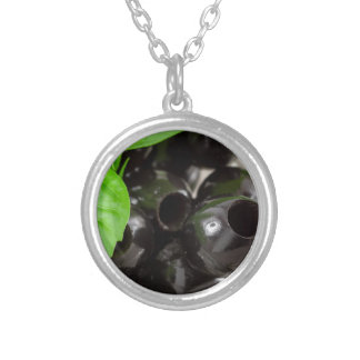 Black olives, pitted marinated in a glass bowl silver plated necklace