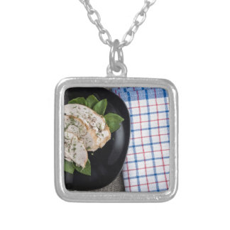 Black plate and baked slices of chicken meat silver plated necklace