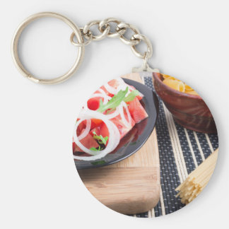 Black plate with fresh salad of tomatoes, onions basic round button keychain