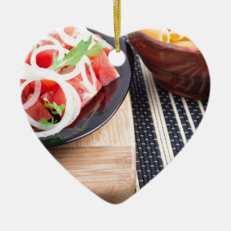 Black plate with fresh salad of tomatoes, onions ceramic heart ornament