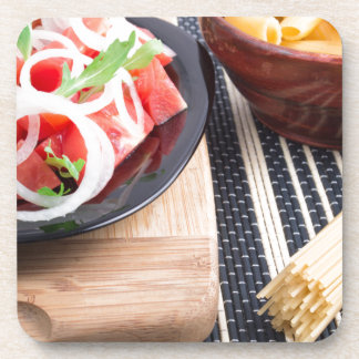 Black plate with fresh salad of tomatoes, onions drink coaster