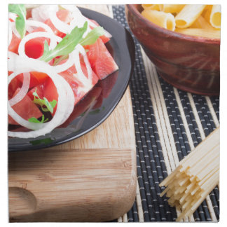 Black plate with fresh salad of tomatoes, onions napkin