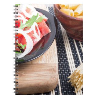 Black plate with fresh salad of tomatoes, onions notebook