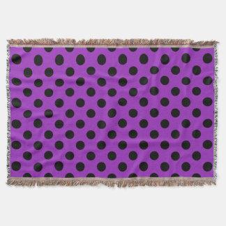 Black polka dots on purple throw