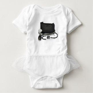 Black professional blood pressure monitor on white baby bodysuit