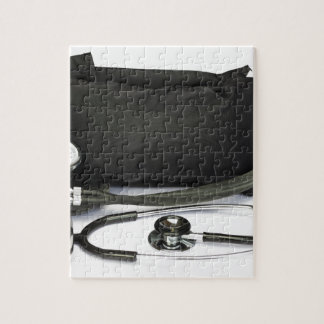 Black professional blood pressure monitor on white jigsaw puzzle