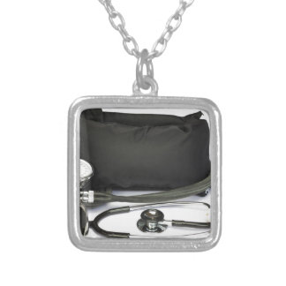 Black professional blood pressure monitor on white silver plated necklace