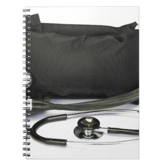 Black professional blood pressure monitor on white spiral notebooks