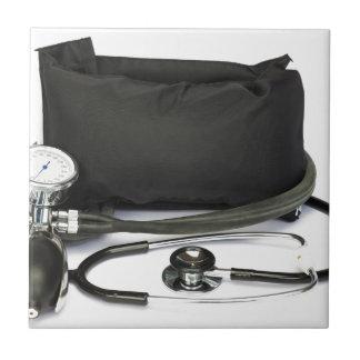 Black professional blood pressure monitor on white tile