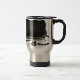 Black professional blood pressure monitor on white travel mug