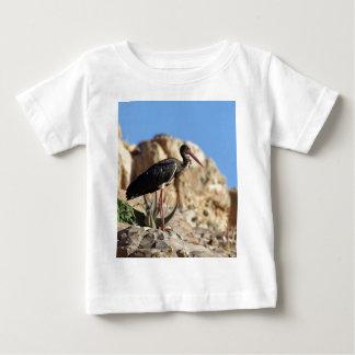 Black stork (Ciconia nigra) on a rock. Baby T-Shirt