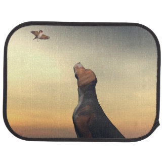 Black tan dog looking a bird flying car mat