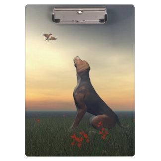 Black tan dog looking a bird flying clipboard