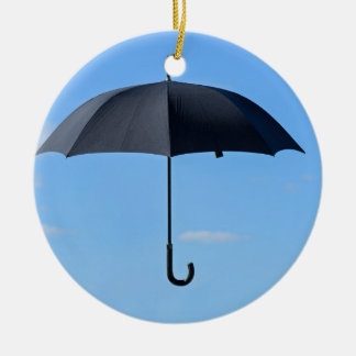 Black umbrella flies in blue sky ceramic ornament
