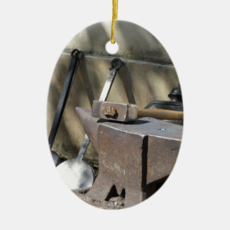 Blacksmith hammer resting on the anvil ceramic oval ornament