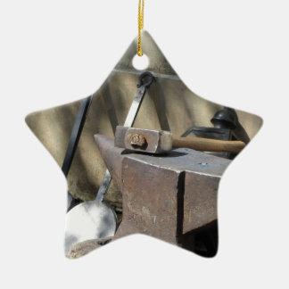 Blacksmith hammer resting on the anvil ceramic star ornament