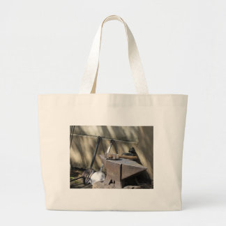 Blacksmith hammer resting on the anvil large tote bag