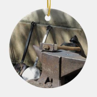 Blacksmith hammer resting on the anvil round ceramic ornament