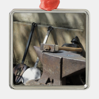 Blacksmith hammer resting on the anvil Silver-Colored square ornament