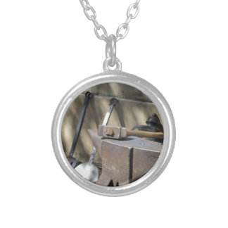 Blacksmith hammer resting on the anvil silver plated necklace