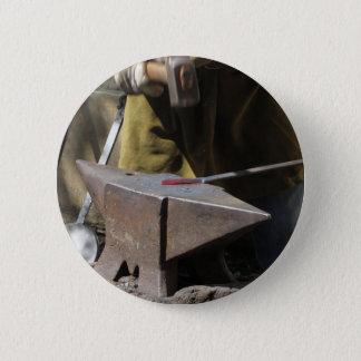 Blacksmith manually forging the molten metal 2 inch round button